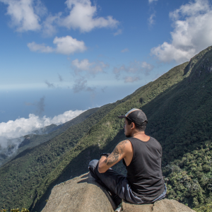 man sitting on top of a mountain after doing exercises for boosting male fertility